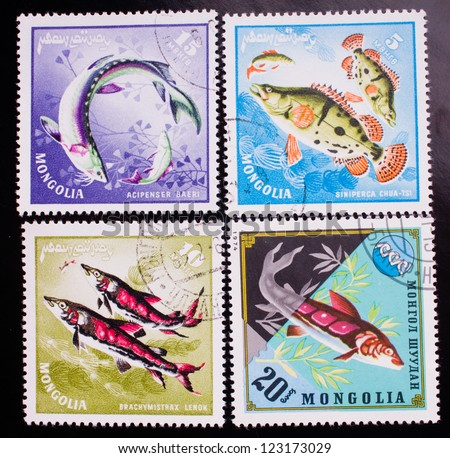 MONGOLIA - CIRCA 1974: A stamp printed in Mongolia shows four kinds of swimming sea fish , circa 1974. - stock photo