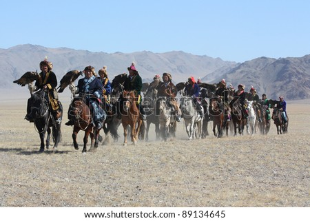 """MONGOLIA - 25 JULY: Senior Mongolians horsemen in traditional clothing with golden eagles during the festival of name """"The Golden Eagle Festival"""" July 25, 2011, Mongolia - desert - stock photo"""