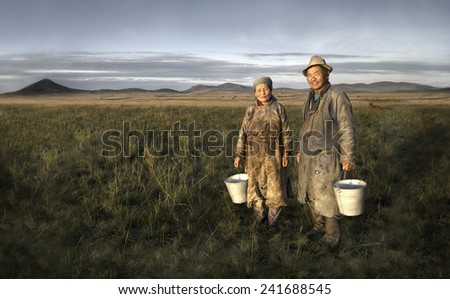 Mongolian couple farmers holding basin and posing in the field. - stock photo
