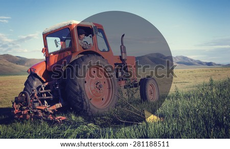 Mongolian farmer driving his tractor on the field. - stock photo
