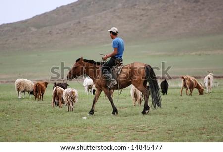 Mongolian goat herdsmen on horseback - stock photo