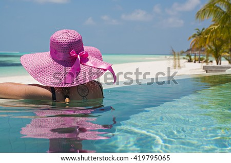 Monika enjoying her holiday in the infinity pool of Kuredu, maldives - stock photo