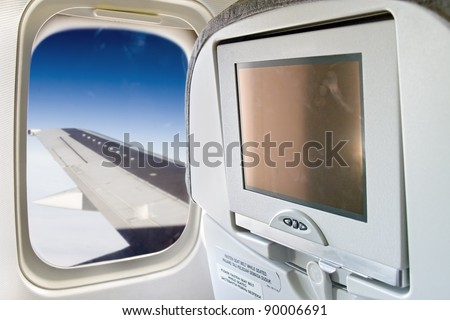monitor and a window on the plane. Wing aircraft flying in the sky in a window plane. Blank display screen on the aircraft seat by the window. - stock photo