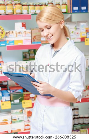 Monitor availability of medicine. Portrait of blonde pharmacist or health care worker with clipboard standing in a drugstore - stock photo