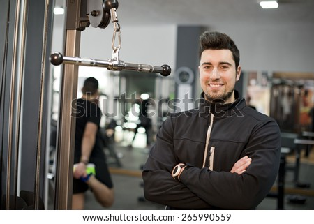 Monitor fitness trainer posing and smiling looking at camera - stock photo