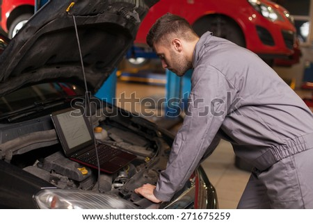 Monitor the Operation of the Engine. Focused auto mechanic looking on a computer connected to a car engine. Waist up shot in auto repair shop. - stock photo