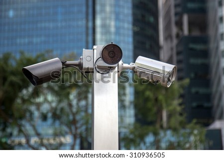 monitoring cameras on the streets of Singapore. Outdoor CCTV in the city center. Police cameras patrol watching order on street. CCTV on the pillar near skyscrapers. - stock photo