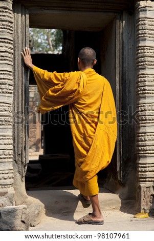 Monk go through the entrance to Angkor Wat. - stock photo