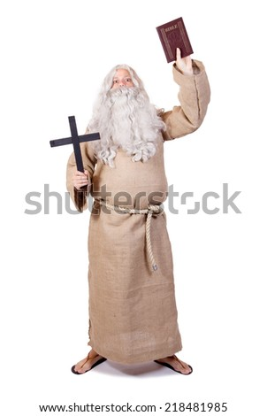 Monk holding a Bible on white background. The bearded prophet with Bible in hand and cross on white background. Visionary shows Christian cross and the Bible. Warning preacher with Christian symbols. - stock photo