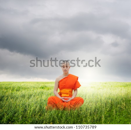 Monk meditating in grass fields and rainclouds - stock photo