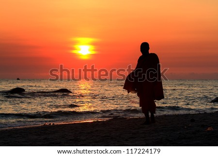 Monk on Hua Hin beach with silhouette