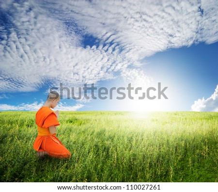 Monk pray in grass fields and blue sky - stock photo