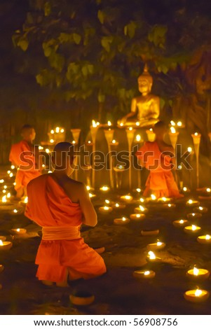 Monk pray to buddha statue and candle in Chiangmai Thailand - stock photo