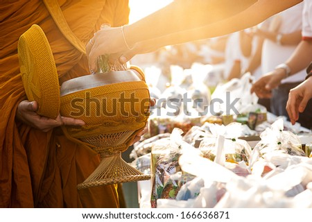 Monk receiving food and items offering from people - stock photo