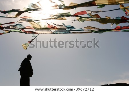 monk silhouette and tibet buddhist flag - stock photo