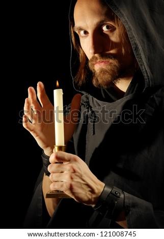 monk with burning candle, shot over black background - stock photo