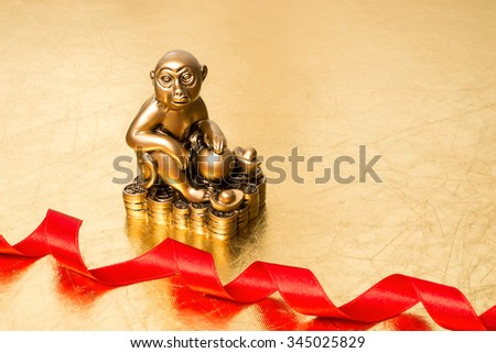 Monkey is a symbol of the chinese new year 2016, and red  satin ribbon on a gold background - stock photo