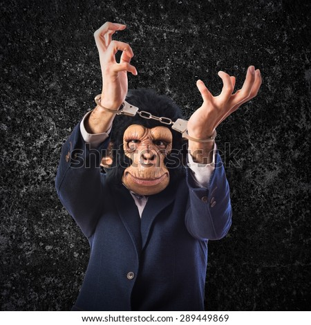 Monkey man with handcuffs over textured background   - stock photo