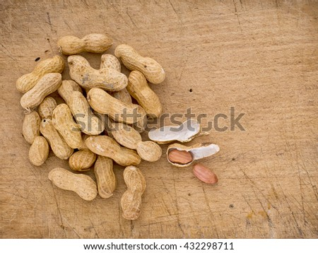 Monkey nuts, groundnuts, peanuts in shells. On old wooden board background.