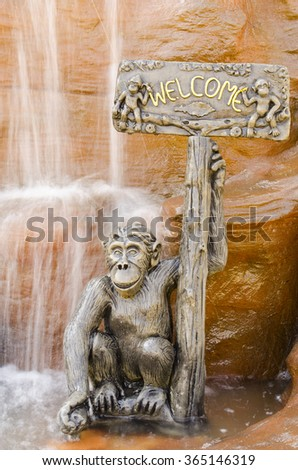 Monkey statue holding a welcome sign.