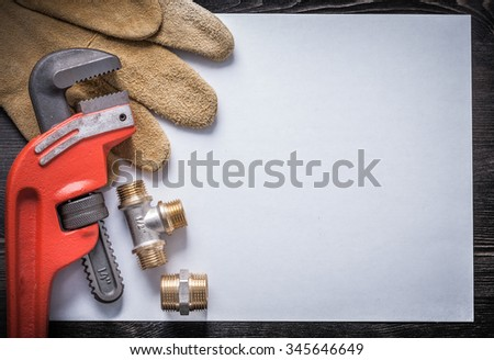 Monkey wrench brass plumbing fittings leather safety gloves clean paper. - stock photo