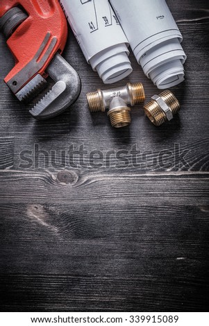 Monkey wrench copper plumbing fixtures blueprint rolls. - stock photo