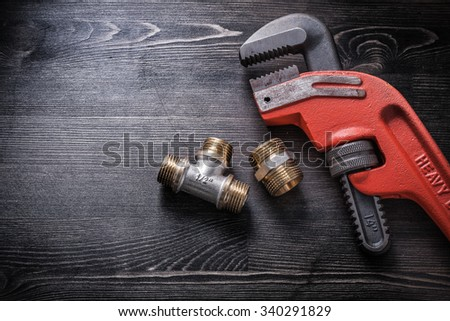 Monkey wrench plumbing fittings on wooden board. - stock photo