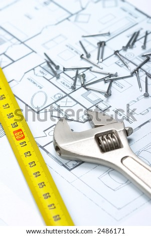 Monkey wrench, tape measure and nails on top of floor plan