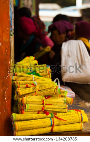 Monks gather to purchase mass produced yellow Tibetan prayer scrolls at a store in Zhongdian, China - stock photo