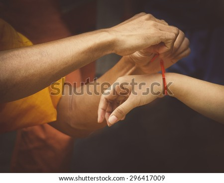 monks giving blessings for peace & luck by tie white or red cotton type string around the wrist of people in Cambodia, Laos, Thailand - stock photo