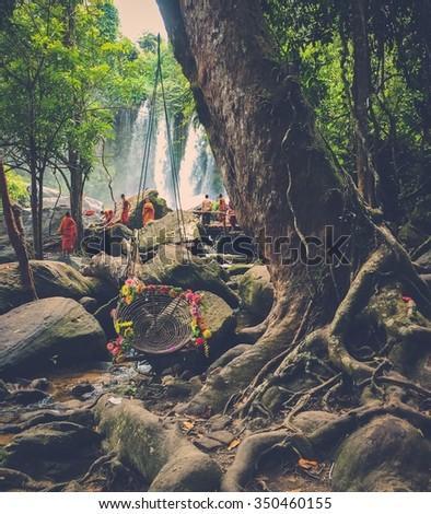 Monks meditating at the tropical waterfall, Phnom Koulen, Siem Reap, Cambodia - stock photo