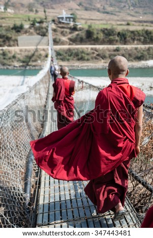 Monks or well know as Lama in Tibet walking on the bridge, Bhutan - stock photo