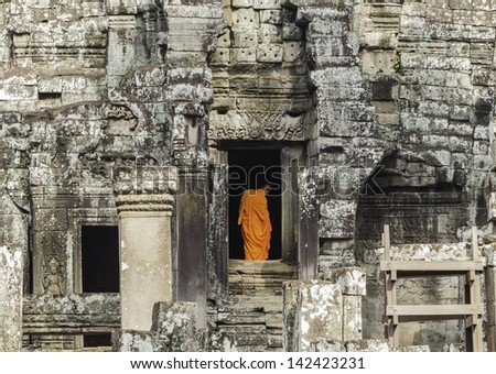 Monks walk through passageways at Angkor wat, Cambodia - stock photo