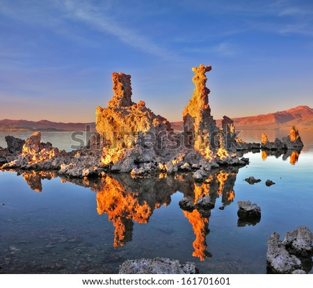 Mono Lake - a natural wonder in the United States. Outliers - bizarre limestone calcareous tufa formation  reflected in the smooth water. - stock photo