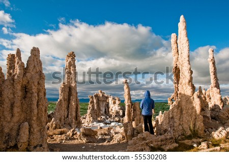 Mono Lake Tufa formations with person to give scale on how low Mono Lake water level currently is - stock photo