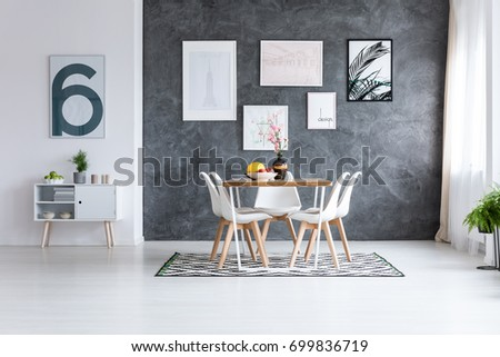 Monochromatic Dining Room With White Cupboard Against White Wall And  Pictures On Dark Wall