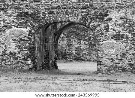Monochromatic photo of of  old ruins built with stone bricks  with a gate with an arc in the center giving view across the ruins - stock photo