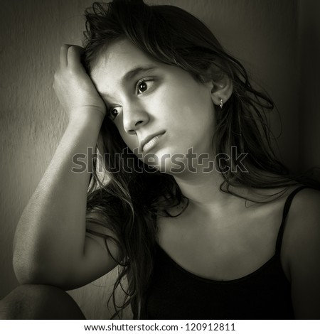 Monochromatic portrait of a sad hispanic girl sitting in a corner with a dirty wall background