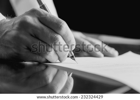 Monochrome close up image of the hands of a businessman signing a business document with a fountain pen.
