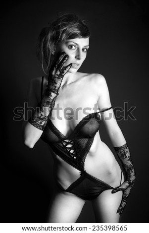 Monochrome fashion portrait of a beautiful woman in sexy lingerie in front of black background - stock photo