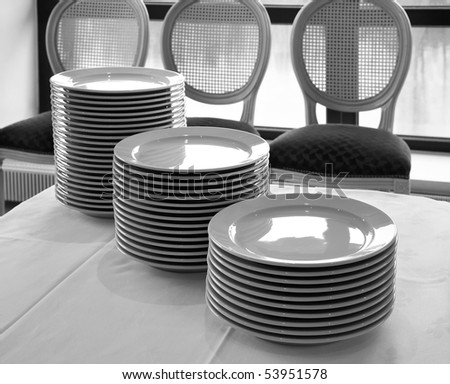 Monochrome group of white plates on table opposite to round backs of chairs - stock photo