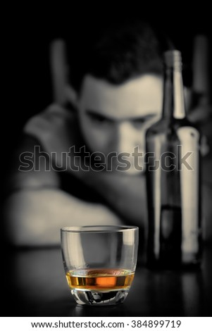Monochrome image of a lonely and sad man drinking alone - stock photo