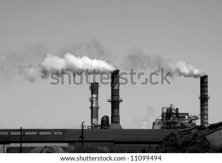 Monochrome image of factory smokestacks belching smoke and soot into the air