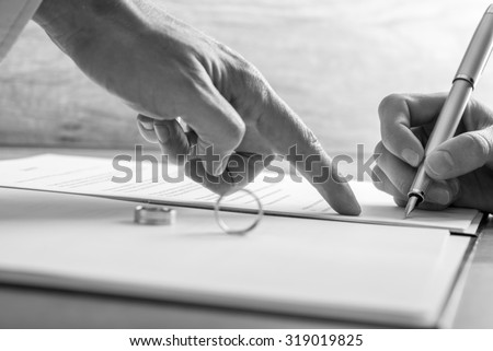 Monochrome image of male hand pointing to a woman where to sign legal divorce papers or marriage registry with wedding rings on the document. - stock photo