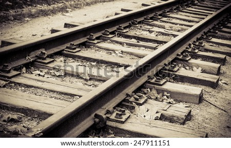 Monochrome image of the railway. Railroad tracks on retro style for travel concept. Old rail road on vintage photo, sepia image. - stock photo