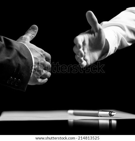 Monochrome image of two businessmen about to shake hands over a signed contract. - stock photo