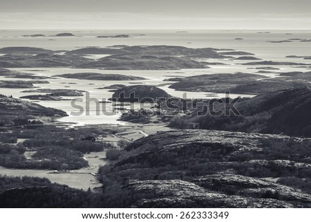 Monochrome Norwegian coastal landscape with sea and small islands in fjord - stock photo