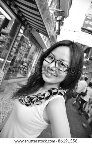 monochrome of a girl on a busy shopping street - stock photo