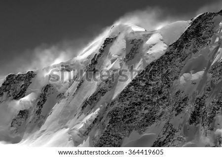 Monochrome of Liskamm in southern switzerland, showing dangerous corniches of ice, caused by strong winds. - stock photo