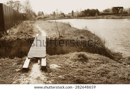 monochrome old photo of village pond and wooden bridge - stock photo